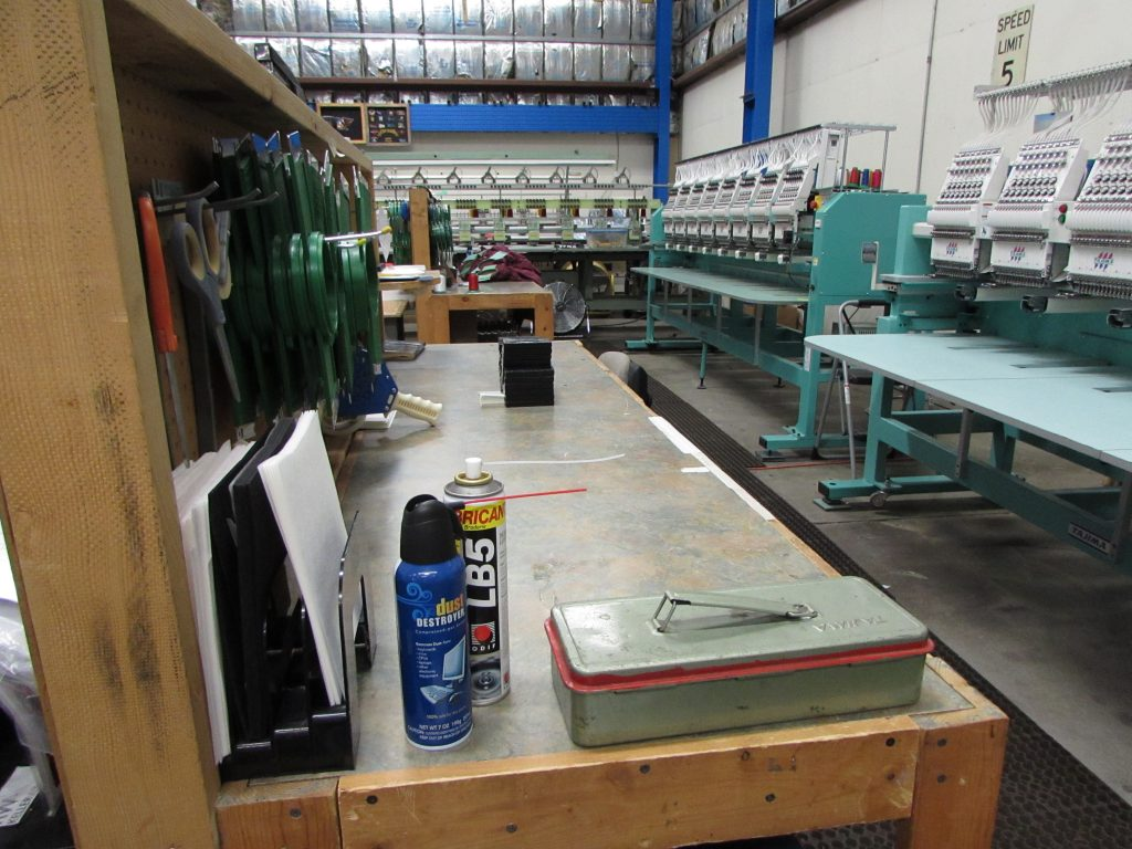 Though they may look a little rough, these home-build workstations across from the embroidery machines have a peg-board backer that holds all the most-used hoops, scissors, tools, stabilizers, and support materials as well as offering a stable surface on which to work or clamp a hooping station. Everything an operator needs for an average job is within arm's reach, or less than two healthy strides from the control panel.