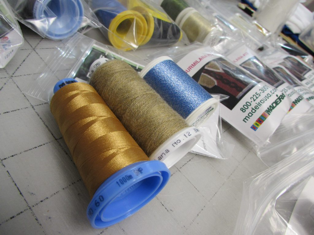 Samples provided by manufacturers provide a low-cost way to test and promote new materials and techniques; here, 60wt thread, thick wool-blend thread, and a metallic-infused twist thread from sample kits are on-deck for testing.
